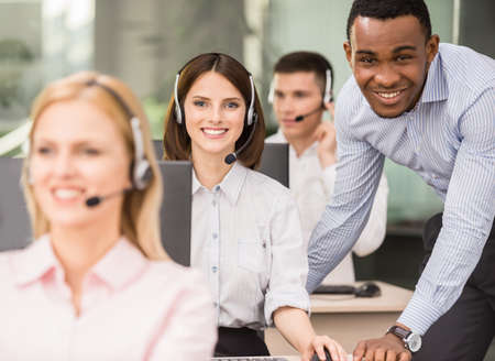 Photo for Manager explaining something to his employee in a call centre. - Royalty Free Image