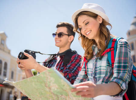 Young tourist couple with map looking for a way and making photos ot the city.