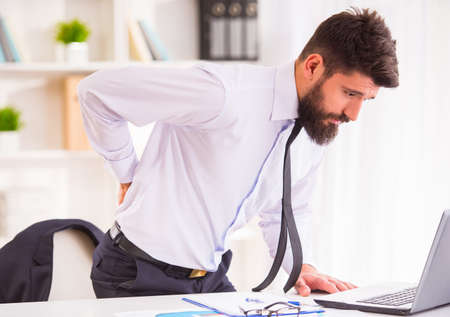 Disease back. Portrait of a businessman with a beard while working in his office, holding behind his back