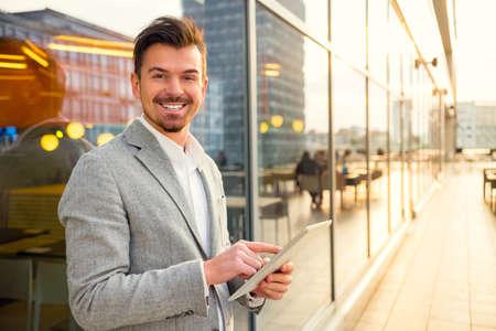 Foto de Portrait of a young successful businessman on background of office center - Imagen libre de derechos