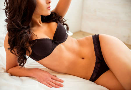 Photo for Beautiful young girl in black lingerie posing on the bed at home - Royalty Free Image