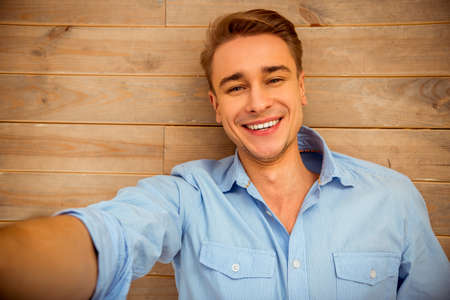Photo pour Young handsome man in the blue shirt, lying on the wooden floor, smiling, taking pictures of themselves. Close-up - image libre de droit