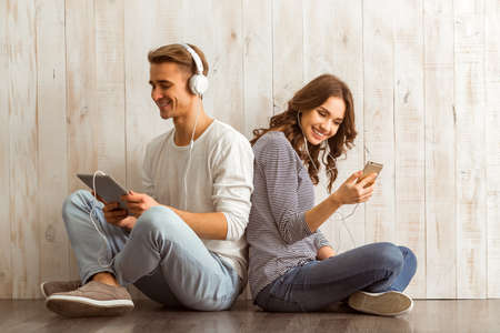 Photo pour Girl using smartphone, and the guy using a tablet with headphones listening to music and leaning on each other, sit on wooden floor at home - image libre de droit
