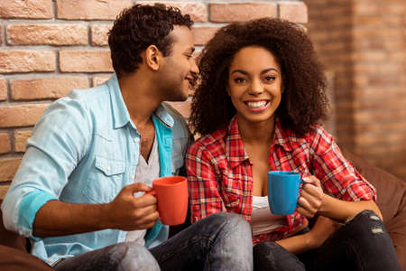 Photo pour Attractive Afro-American couple drinking coffee, talking and laughing while sitting on chair against brick wall - image libre de droit