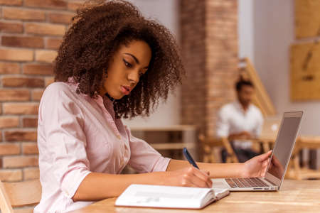 Photo pour Young beautiful Afro-American businesswoman using laptop and writing in notebook while studying in cafe - image libre de droit
