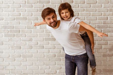 Photo for Portrait of a handsome father carrying his cute son on back. Both in white t-shirts smiling, standing against white brick wall. - Royalty Free Image