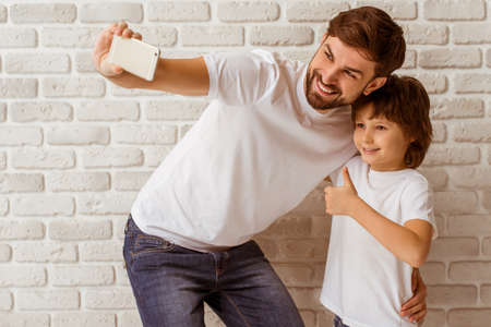 Photo for Handsome young father making a photo with his cute little son. A little boy showing OK sign. Both in white t-shirts smiling, standing against white brick wall. - Royalty Free Image