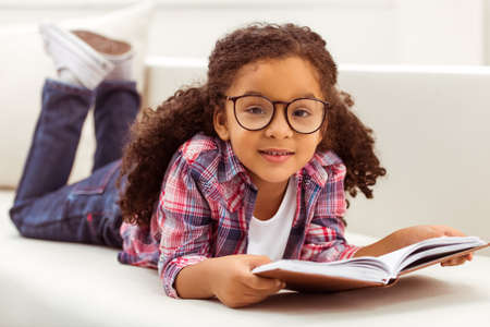 Photo pour Cute little Afro-American girl in casual clothes and eyeglasses reading a book, looking at camera and smiling while lying on a sofa in the room. - image libre de droit