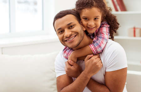 Photo for Cute little Afro-American girl in casual clothes cuddling her handsome father. Both looking at camera and smiling. - Royalty Free Image