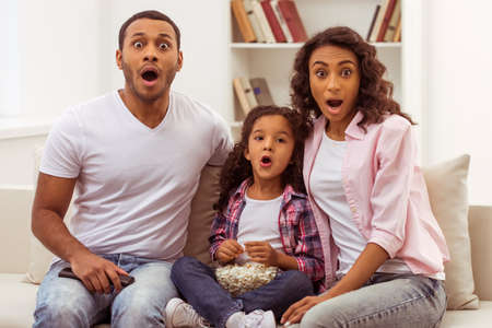 Photo pour Cute little Afro-American girl and her beautiful young parents looking at camera and showing surprise while sitting on a sofa and watching TV. Father holding a remote control, daughter holding a bowl with popcorn. - image libre de droit