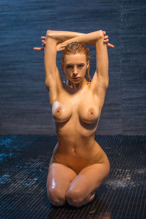 Photo for Passionate beautiful young naked woman enjoying pleasant shower, sitting on her knees, keeping hands up and looking at camera - Royalty Free Image