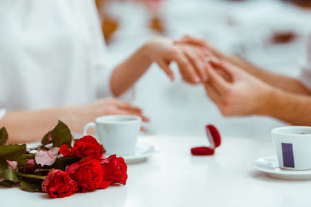 Photo for Handsome man putting wedding ring on and proposing to his beautiful woman in cafe. Bunch of red roses on a table, close-up - Royalty Free Image