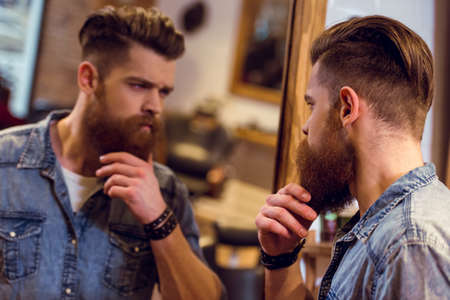 Photo for Handsome young bearded barber  looking in the mirror and adjusting his beard while standing in the barber shop - Royalty Free Image