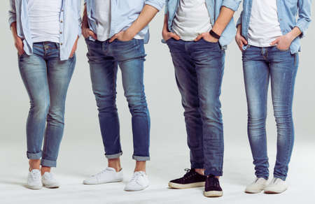 Young people in jeans standing on a gray background, legs close-up