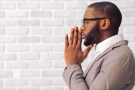 Photo pour Side view of handsome Afro American man in classic suit and glasses keeping palms together like praying, standing against white brick wall - image libre de droit