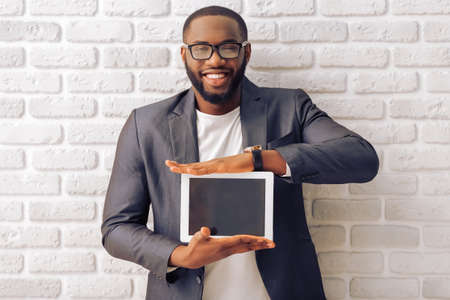 Foto de Handsome Afro American businessman in gray classic jacket and glasses is showing a tablet and smiling, standing against brick wall - Imagen libre de derechos
