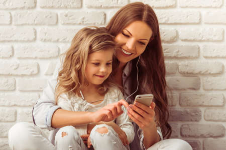 Photo pour Beautiful young mother and her cute little daughter are listening to music using a smart phone and smiling, against white brick wall - image libre de droit
