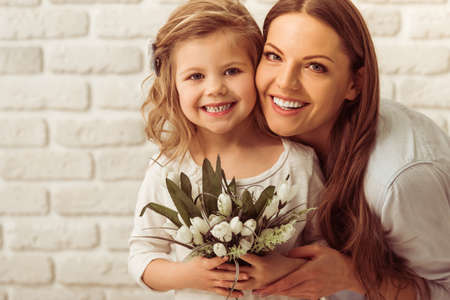 Photo pour Beautiful young mother and her cute daughter are looking at camera and smiling, against white brick wall. Little girl is holding flowers - image libre de droit