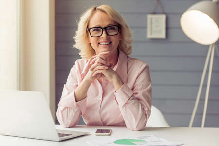 Photo pour Beautiful old woman in classic shirt and glasses is looking at camera and smiling while working with a laptop at home - image libre de droit