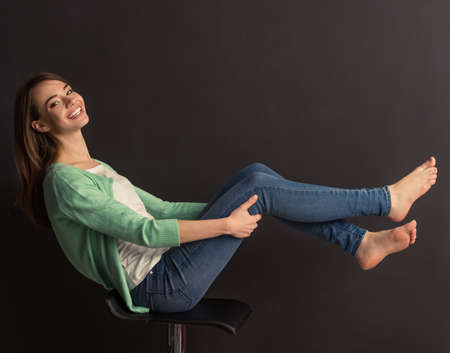 Photo pour Side view of beautiful young girl looking at camera and smiling, sitting with raised legs on chair against dark background - image libre de droit