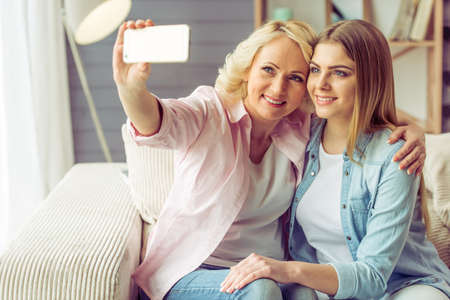 Photo for Portrait of beautiful mature mother and her daughter making a selfie using a smart phone and smiling, sitting on sofa at home - Royalty Free Image