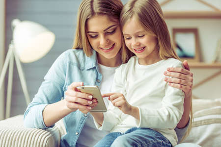Foto de Beautiful young mom and her little daughter are using a smartphone and smiling while sitting on sofa at home - Imagen libre de derechos