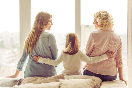 Photo pour Back view of three generations of beautiful women sitting on sofa against window - image libre de droit