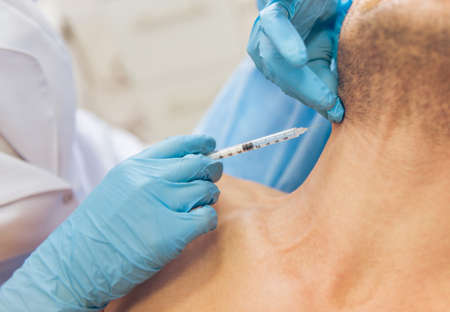 Photo pour Doctor in medical gloves is giving an injection in man neck, close-up - image libre de droit
