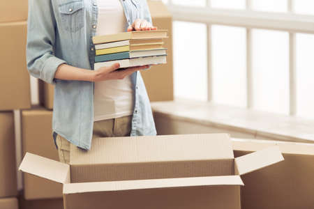 Photo pour Cropped image of attractive young woman moving, packing books in cardboard box, looking at camera and smiling - image libre de droit