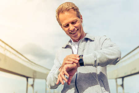Foto de Handsome middle aged man in sports uniform and headphones is looking at his watch and smiling during morning run - Imagen libre de derechos