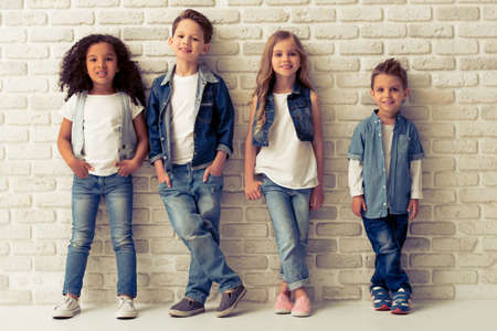 Foto de Full length portrait of cute little kids in stylish jeans clothes looking at camera and smiling, standing against white brick wall - Imagen libre de derechos