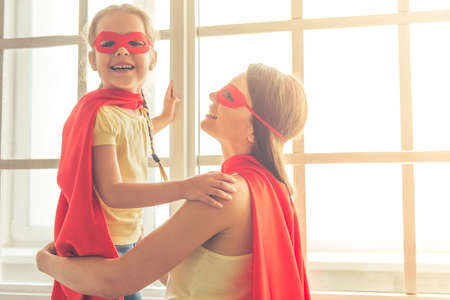 Photo for Beautiful mother and her little daughter dressed like superheroes are smiling while playing at home - Royalty Free Image