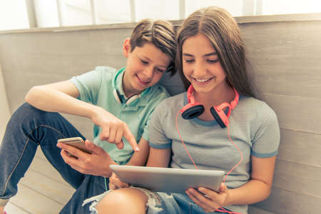 Photo for Teenage boy and girl with headphones are using gadgets, talking and smiling while sitting on the floor - Royalty Free Image