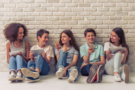 Photo pour Group of teenage boys and girls is using gadgets, talking and smiling, sitting against white brick wall - image libre de droit