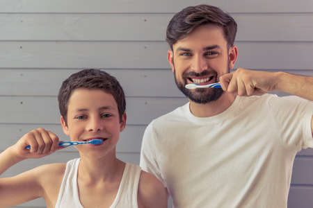 Photo pour Handsome young father and his teenage son are brushing teeth, looking at camera and smiling, against gray wall - image libre de droit