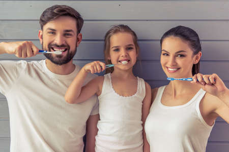 Photo pour Beautiful young parents and their cute little daughter are looking at camera and smiling while brushing teeth, against gray wall - image libre de droit