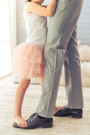 Photo for Cropped image of young father and his cute little daughter dancing at home. Girl is standing on her father's feet - Royalty Free Image