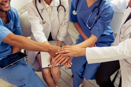 Cropped image of medical doctors of different nationalities and genders holding hands together and smiling, sitting in office