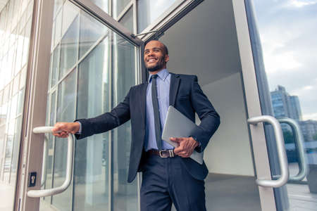 Photo pour Low angle view of handsome young Afro American businessman in classic suit holding a laptop and smiling while leaving the office building - image libre de droit