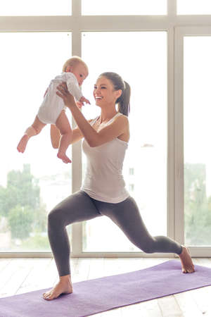 Photo for Beautiful young mom in sports wear is smiling while doing yoga with her charming little baby on a mat against window - Royalty Free Image
