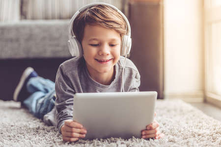 Foto de Little boy in headphones is using a digital tablet and smiling while lying on the floor at home - Imagen libre de derechos