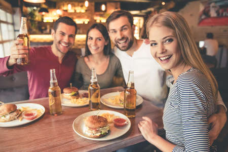 Photo for Happy friends are looking at camera and smiling while spending time together in cafe - Royalty Free Image