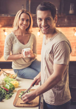 Beautiful woman is drinking tea while her handsome boyfriend is cooking, both are smiling