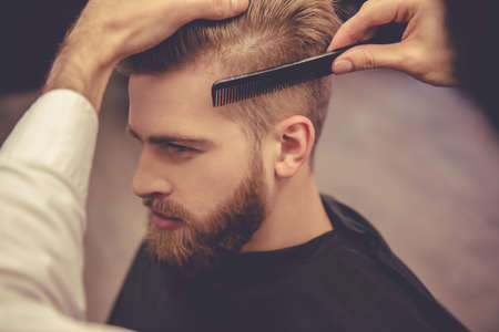 Photo for Handsome bearded man is looking forward while having his hair cut by hairdresser at the barbershop - Royalty Free Image