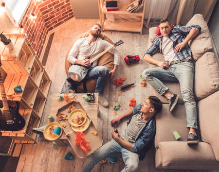 Top view of guys sleeping in messy room after having a party at home