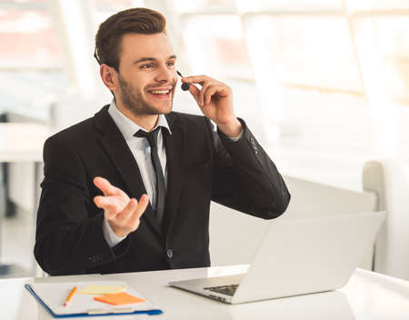 Attractive businessman in suit and headset is talking and smiling while working with laptop in office