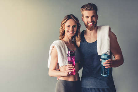 Foto de Beautiful young sports people are holding bottles of water, looking at camera and smiling, on gray background - Imagen libre de derechos