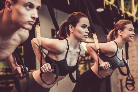 Photo for Beautiful young sports people are working out with TRX in gym - Royalty Free Image