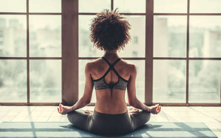 Photo pour Back view of attractive Afro American girl in sportswear sitting in lotus position while doing yoga - image libre de droit