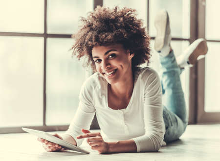 Photo pour Attractive Afro American girl is using a digital tablet, looking at camera and smiling while lying on the floor - image libre de droit